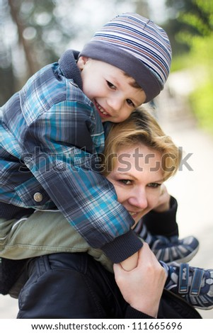 Cute boy and mother smiling at park - stock photo
