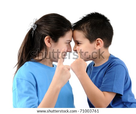 Cute boy and teen girl pointing fingers at each other isolated on white. - stock photo