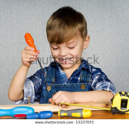 Cute boy as a construction worker, playing with tools - stock photo