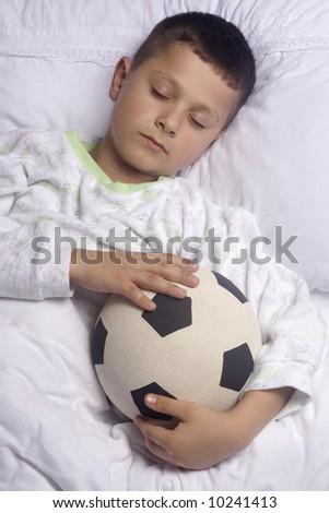 Cute boy asleep with  football - stock photo