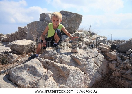 Cute boy building a tower of stones - stock photo