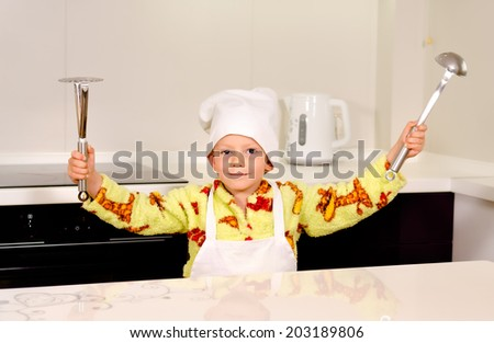 Cute boy chef in a white toque and apron displaying his utensils brandishing a ladle and potato masher in the air before starting to prepare dinner - stock photo