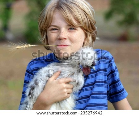 Cute boy child with his splash silkie rooster