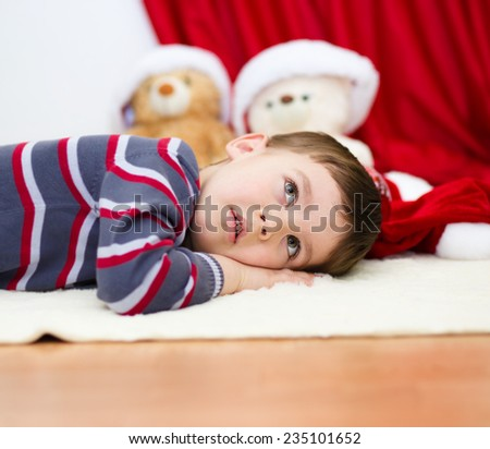 Cute boy daydreaming lying on the floor. Christmas Eve. New Year. Festive mood - stock photo