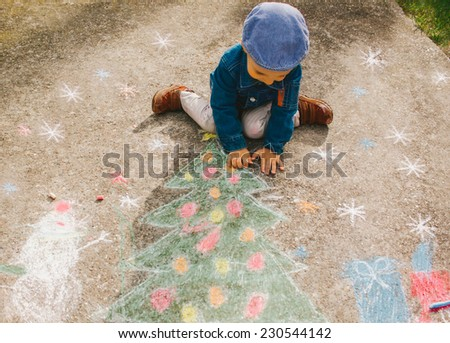 Cute boy drawing Christmas decorations on the street. - stock photo