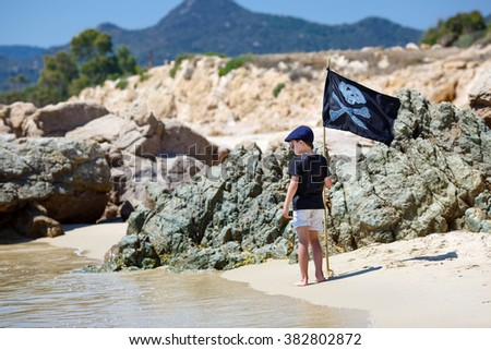 Cute boy dressed as pirate on tropical beach during summer holiday vacation - stock photo