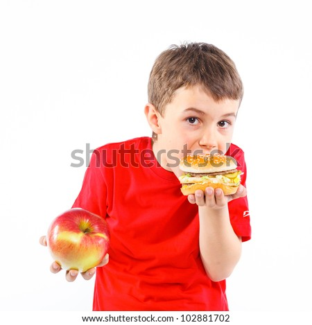 Cute boy eating a hamburger. Isolated on a white background - stock photo