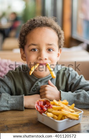 Cute boy eating french fries in restaurant - Funny joke - stock photo