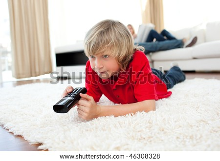 Cute boy holding a remote lying on the floor in the living-room - stock photo