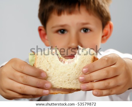 cute boy holding his sandwich . Selective focus on hands and sandwich - stock photo