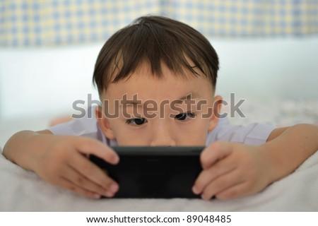 cute boy holding portable games machine. - stock photo