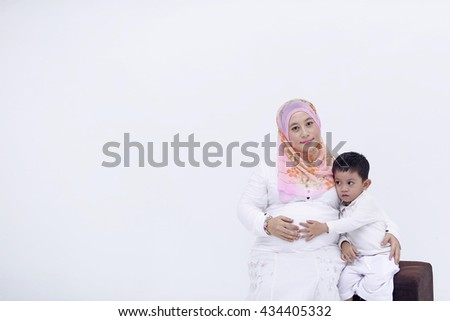 Cute boy hugging belly pregnant mother on white background