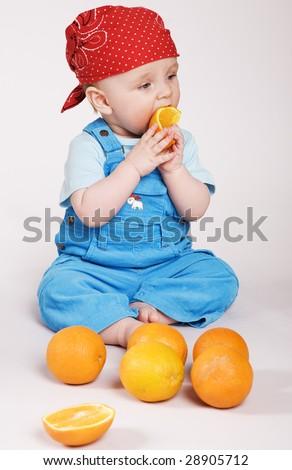 Cute boy in bandana eating orange - stock photo