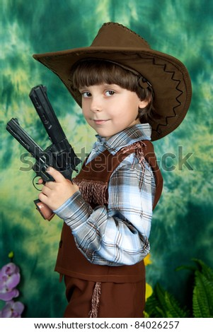 cute boy in cowboy costume with guns on a green background