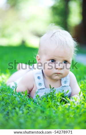 cute boy in green grass - stock photo