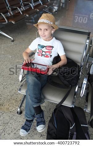 Cute boy in hat listening music in airport - stock photo