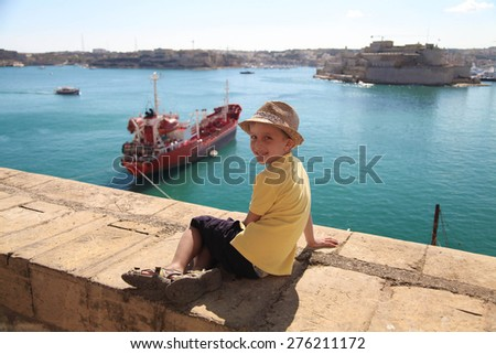 Cute boy in hat looking at ship in harbor of Malta - stock photo