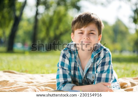 Cute boy in summer park lying on blanket and reading book - stock photo
