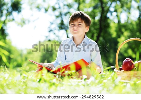 Cute boy in summer park sitting on blanket and reading book