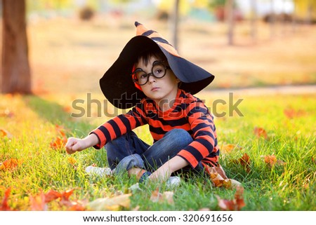 Cute boy in the park with halloween costume, hat and glasses, having fun autumn time - stock photo
