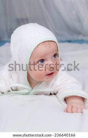 Cute boy in white bathrobe lying on sofa, close up - stock photo