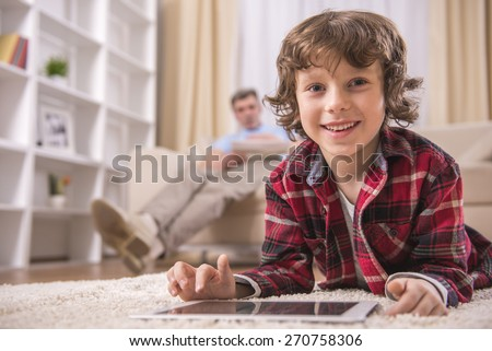 Cute boy is playing with tablet. Grandfather on background. - stock photo