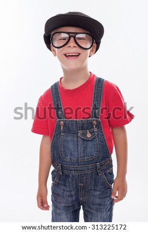 Cute boy is standing in funny hat and huge eyeglasses. He is looking forward and laughing. Isolated on background - stock photo