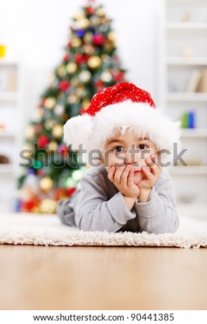 Cute boy laying in front of decorated Christmas tree - stock photo