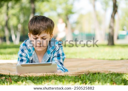 Cute boy lying in park and using tablet pc - stock photo
