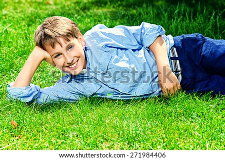 Cute boy lying on a grass at a park and smiles. Summer day. Holiday. - stock photo