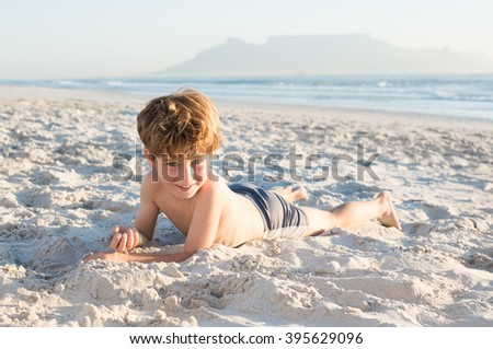 Cute boy lying on front the beach. Portrait of smiling boy looking at camera at seaside. Pretty child playing with sand at beach.