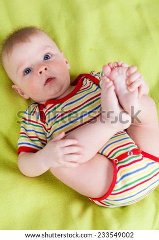 Cute boy lying on his back and holding his feet - stock photo