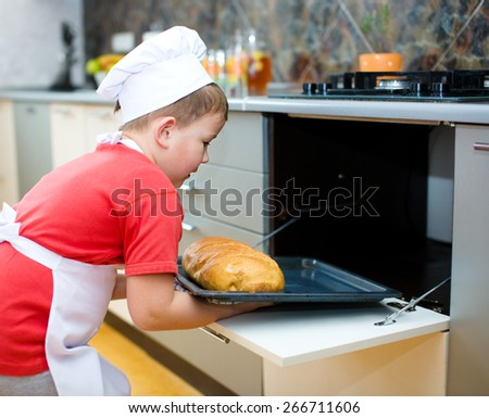 Cute boy making bread in the kitchen