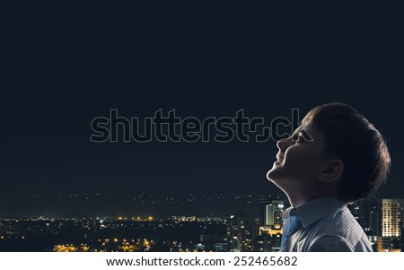 Cute boy of school age against night background - stock photo