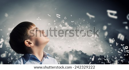 Cute boy of school age and letters flying around - stock photo