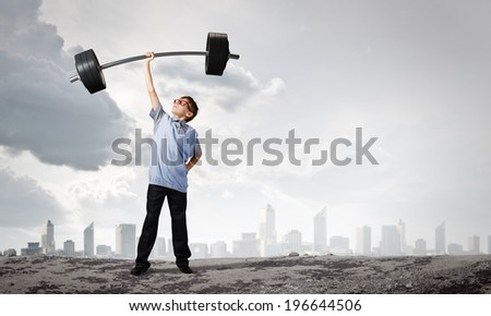Cute boy of school age lifting barbell above head - stock photo
