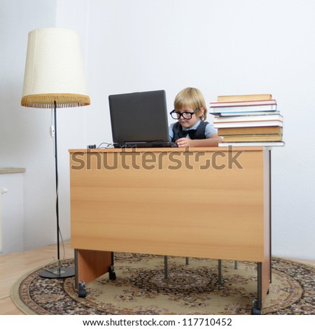 cute boy on laptop at the office desk - stock photo