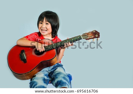 cute boy play guitar.lovely kid play music instrument.happy kid love music isolate on blue background