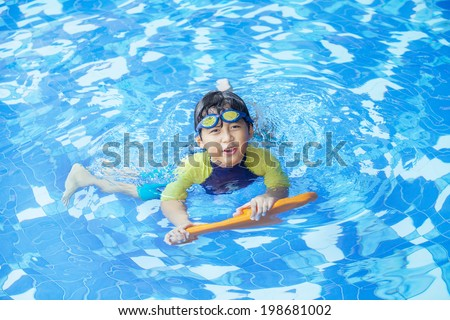 Cute boy playful on the pool and smiling at the camera - stock photo
