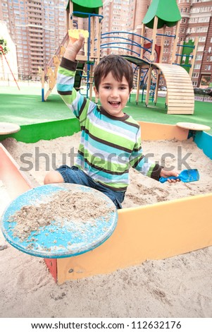 Cute boy playing in sandbox with a sand toys - stock photo