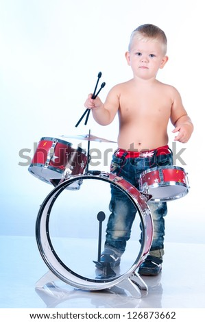 Cute boy playing the drums - stock photo