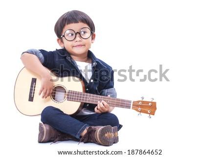 Cute boy playing the ukulele on white background  - stock photo