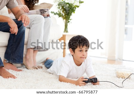 Cute boy playing video game lying on the floor at home with his parents - stock photo