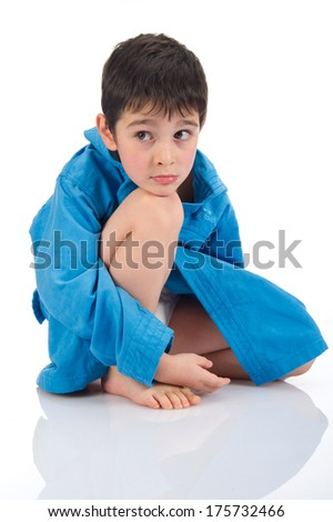 Cute boy playing with a blue bathrobe on white background.