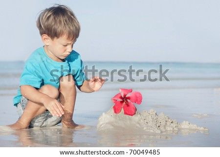 cute boy playing with sand on beach