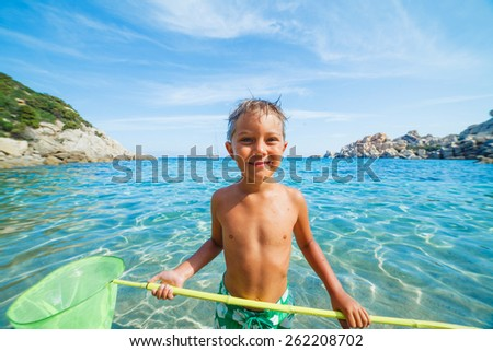 Cute boy playing with scoop-net and swimming in the transparent sea - stock photo