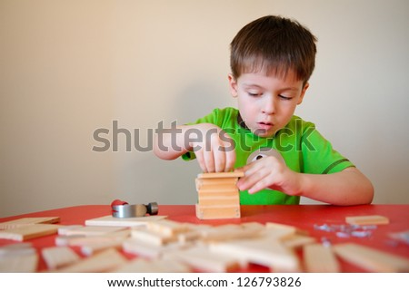 Cute boy playing with wooden kit - stock photo
