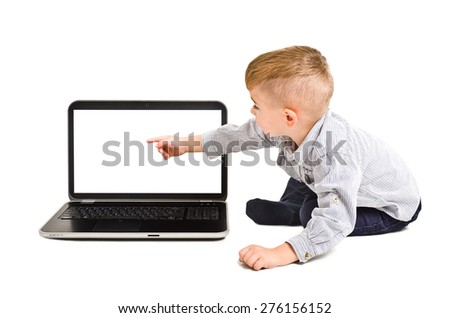 Cute boy points finger at the screen of laptop sitting isolated on white background - stock photo