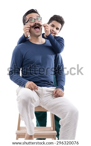 Cute boy pulling his father's mustache isolated on white background. - stock photo