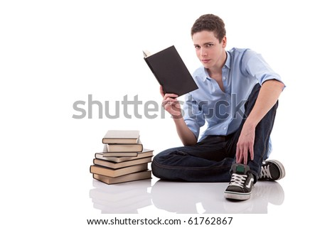 cute boy reading a book on the floor, isolated on white, studio shot